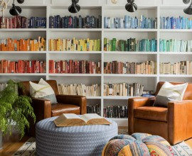 Interior decorator uses books arranged by colour combined with unique furniture and rich leather to create a warm, happy home study.