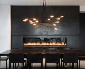 A vintage dining room with industrial accents, modern lighting and furnishings, rich warm colours and a unique feature fireplace for warmth. A minimalist, modern space for the perfect gathering.