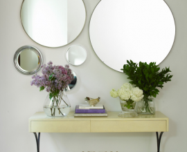 Come home to a classic, country feel, with a touch of modernity achieved by a unique arrangement of circular wall mirrors that bring in both light and a feeling of space, while flowers soften the entire foyer, placed on a vintage writing desk.